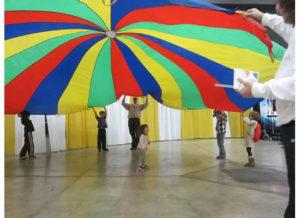 Children enjoy the popular parachute activity at WeatherFest.